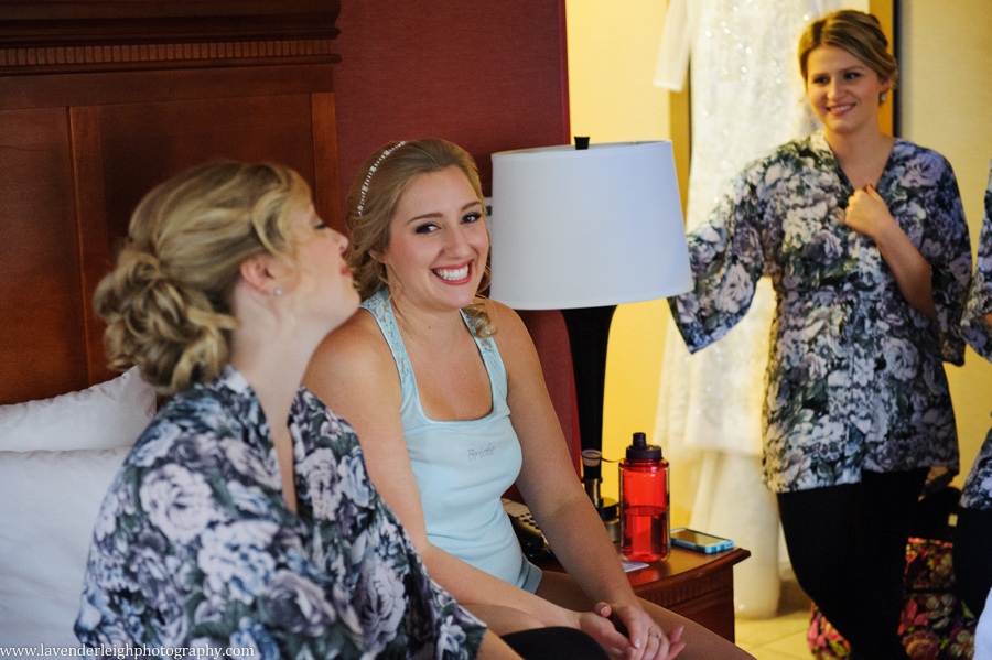 A bride laughing with her bridesmaids before she puts on her winter white wedding dress