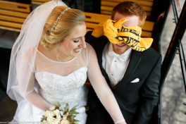 A bride and groom on the trolley, groom is wearing a terrible towel as a blindfold
