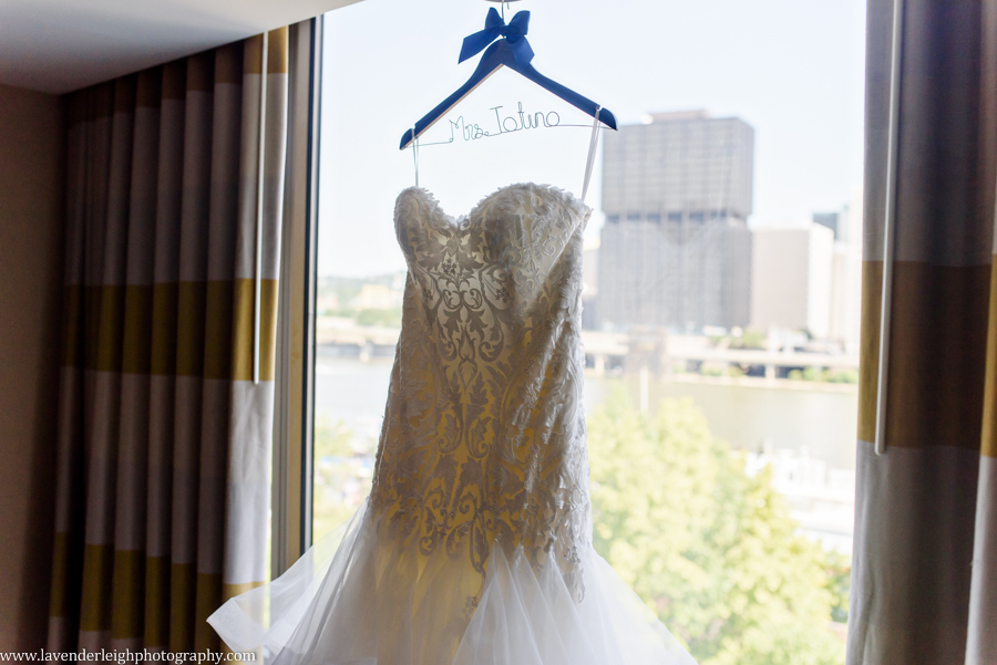 A lace and ruffle wedding dress hanging in a window.