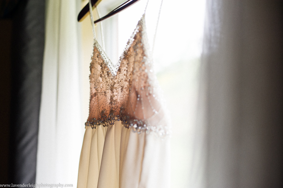 An elegant empire-waist wedding dress hanging in a hotel window.