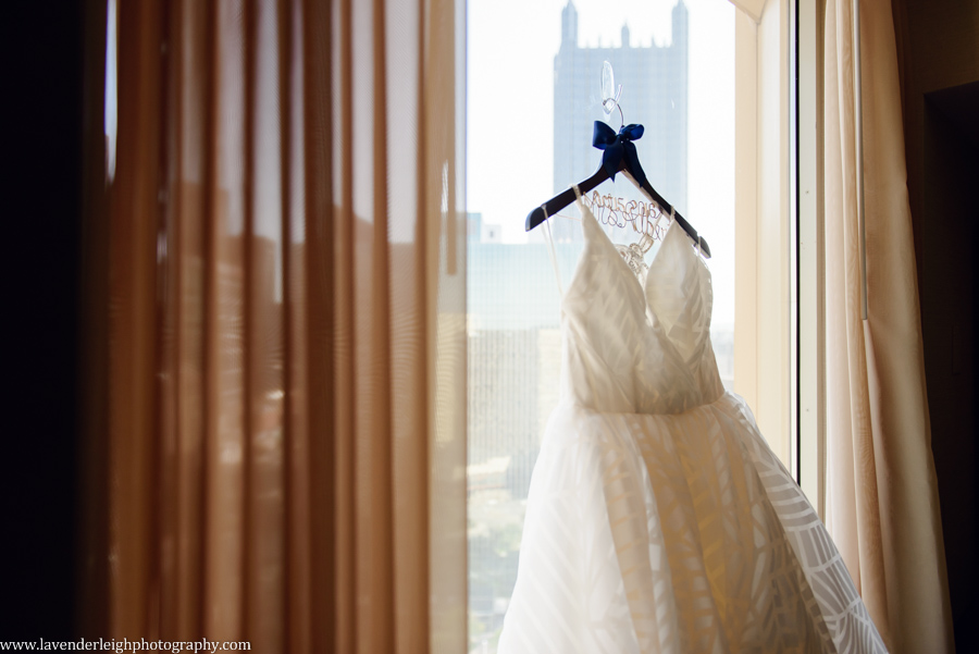The gorgeous Hayley Paige wedding dress hangs in the city window.