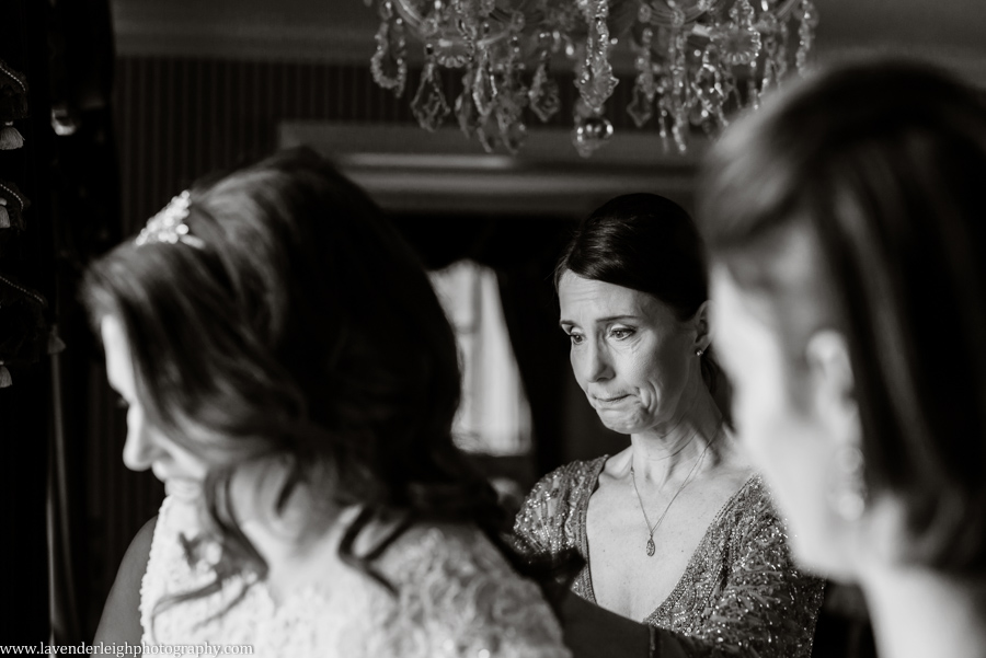 The mother of the bride holds back her tears as she buttons up her daughter