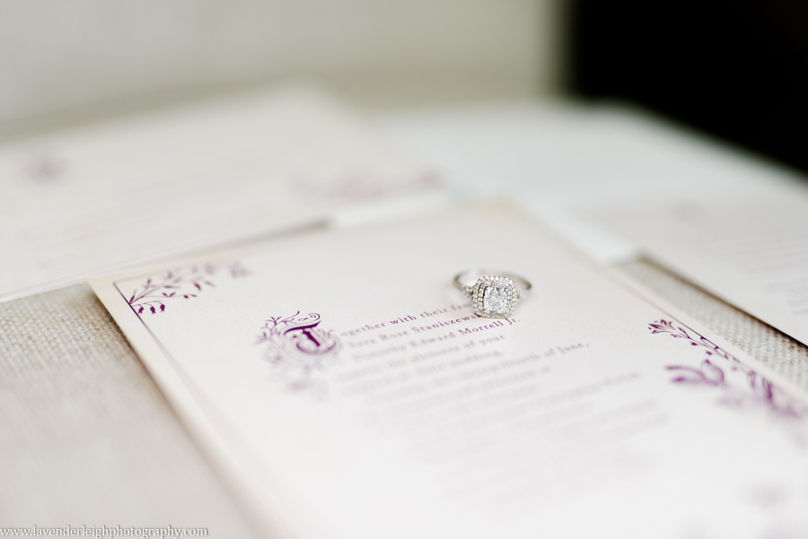 An engagement ring sitting on top of a purple font wedding invitation by Lavender Leigh Photography